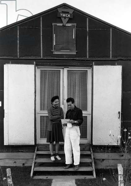 JAPANESE INTERNMENT, 1943 A Japanese American man and woman reading a letter on the steps in front of the Y.M.C.A. at the Manzanar Relocation Center near Owens Valley, California. Photograph by Ansel Adams, 1943.
