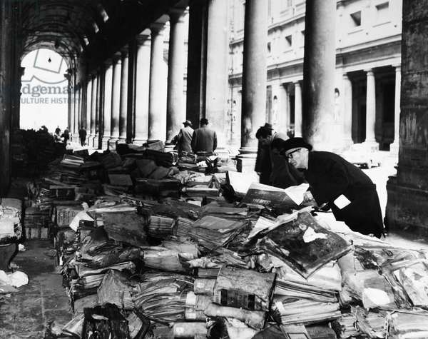 FLORENCE: FLOOD, 1966 Books and manuscripts from the Florence State Archives damaged during the flood of the Arno River, piled in front of the Uffizi Gallery. Photograph 21 November 1966.