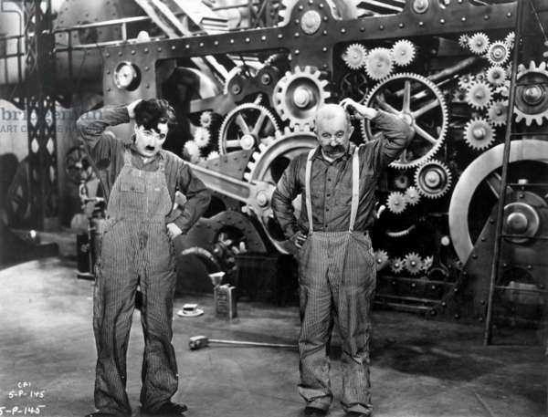 """CHARLIE CHAPLIN and Andy Clyde in a scene from """"Modern Times,"""" 1936."""