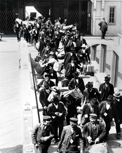 ELLIS ISLAND, c.1910 Immigrants arriving at Ellis Island with their belongings. Photograph, c.1910.