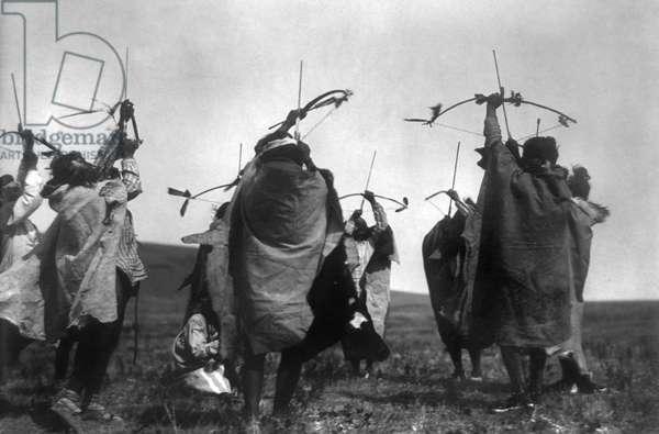 Atsina Native Americans shooting arrows toward the sky during a ritual dance, c.1908 (b/w photo)