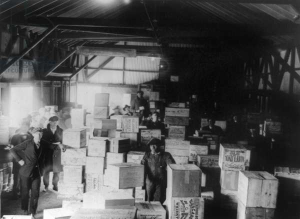 BOOTLEG LIQUOR, 1920s Men standing in a warehouse filled with cases of confiscated moonshine, during Prohibition in America, 1920s.