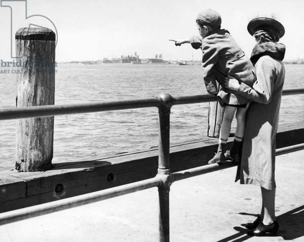 ENEMY ALIEN, 1941 A little boy points to Ellis Island, where his father is detained, having been arrested in a round-up of deportable foreigners on Long Island, New York. Photograph, 18 May 1941.