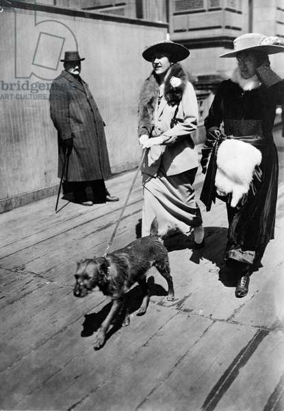 EASTER PARADE, 1915 Two women walk a dog down 5th Avenue during an Easter parade, New York. Photograph, 1915.