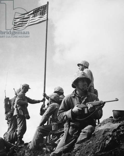 WORLD WAR II: IWO JIMA The raising of the first flag on Mount Suribachi, Iwo Jima, 23 February 1945. The soldiers are Sergeant Henry Hansen (without helmet), Sergeant Ernest Thomas (seated by flagpole), Corporal Charles Lindberg (standing at right), and Private First Class James Michels (on guard with carbine).