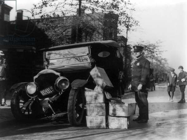 PROHIBITION, 1922 A police officer standing beside a wrecked car and cases of moonshine, 16 November 1922.