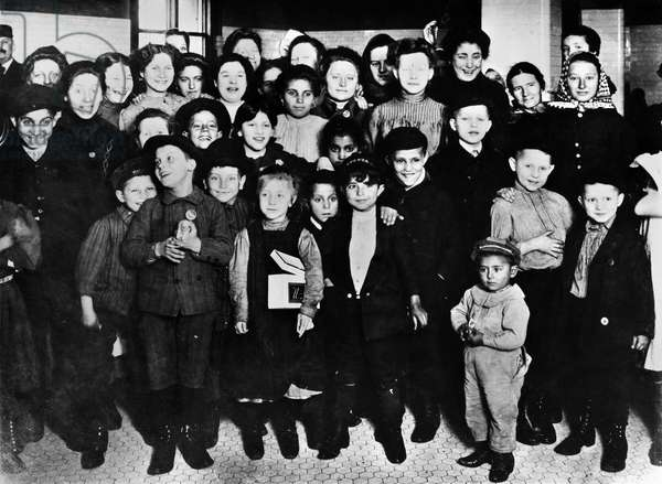 ELLIS ISLAND: IMMIGRANTS Group of happy women and children at Ellis Island, New York City. Photograph, early 20th century.