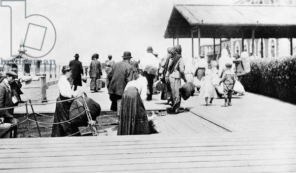 ELLIS ISLAND, c.1915 Immigrants arriving at Ellis Island in New York Harbor. Photograph, c.1915.