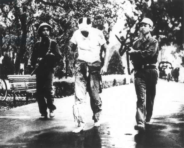 VIETNAM WAR Parading of U.S. prisoner, with bandaged face, walking barefoot between two Vietcong guards.