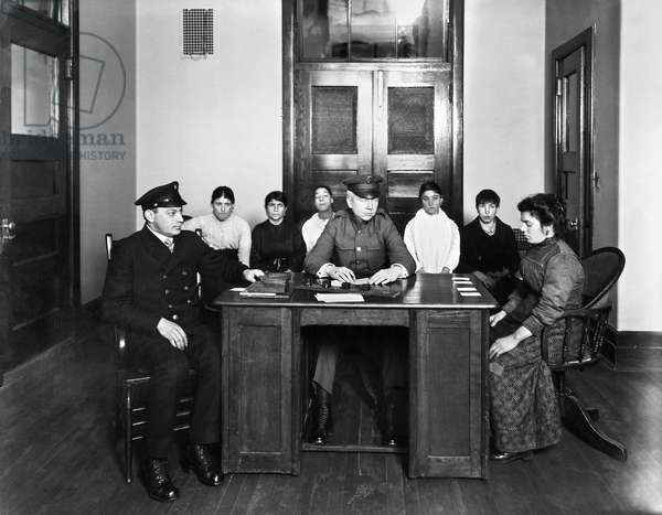 ELLIS ISLAND: IMMIGRANTS Ellis Island officials questioning immigrants. Photograph, early 20th century.