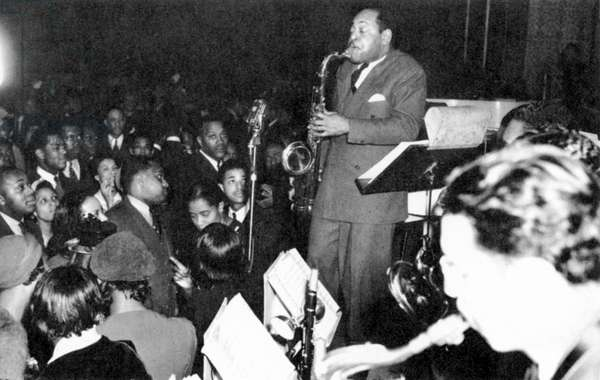COLEMAN HAWKINS (1904-1969) American musician. Hawkins playing the saxophone at a wedding reception in Harlem, New York City, 1940.