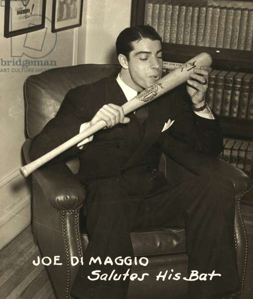 JOE DIMAGGIO (1914-1999) American baseball player. About to kiss his signature baseball bat following the 1941 season, during which he hit safely in a record 56 consecutive games while playing for the New York Yankees.