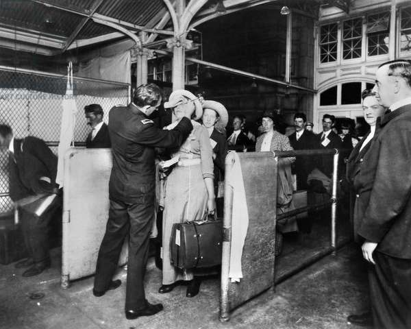 ELLIS ISLAND: EXAMINATIONS Immigrants at Ellis Island being examined for eye diseases. Photograph, early 20th century.