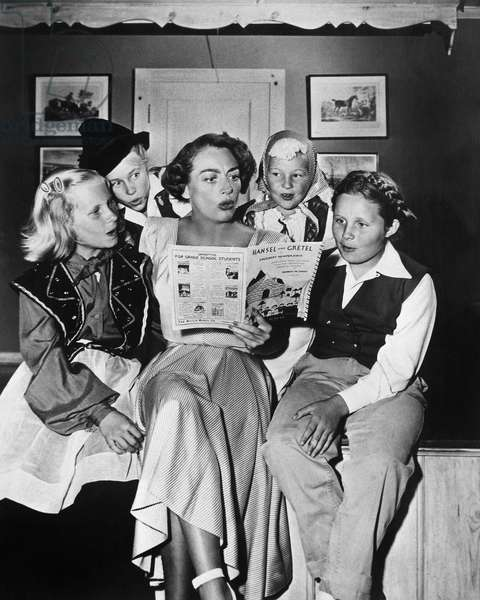 JOAN CRAWFORD (1908-1973) American actress. Crawford directing some young thespians (her daughter, Christina, at left) in the play, Hansel and Gretel, c.1950.