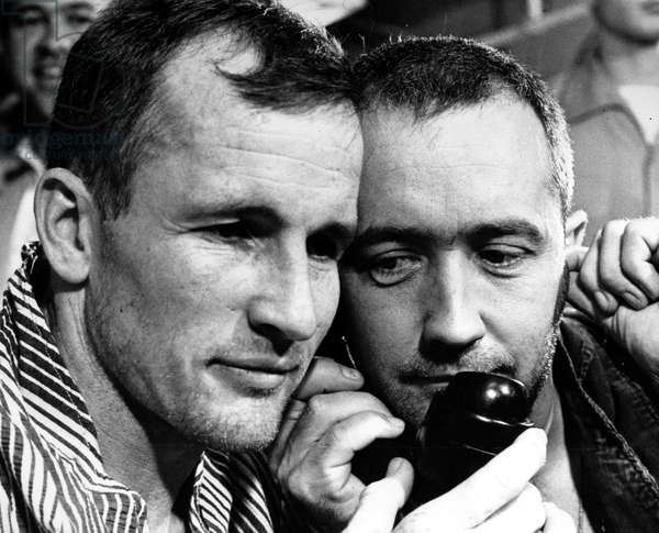 GEMINI IV ASTRONAUTS, 1965 Astronauts Edward White (left) and James McDivitt talk to U.S. President Lyndon Johnson on the ship-to-shore phone aboard the USS Wasp, after completing their Gemini IV mission, 7 June 1965.