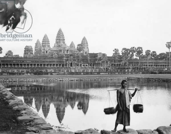 CAMBODIA: ANGKOR WAT A boy outside of the Angkor Wat temple complex in Angkor, Cambodia. Photograph by Ewing Galloway, early to mid 20th century.