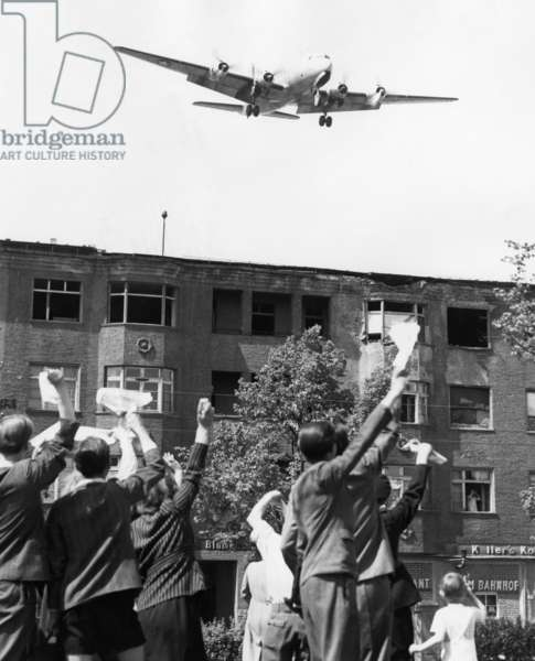 BERLIN: AIRLIFT, 1949 Berliners wave to an American airlift plane approaching Tempelhof Airfield for a landing, 5 May 1949, after the announcement of the lifting of the Berlin blockade.