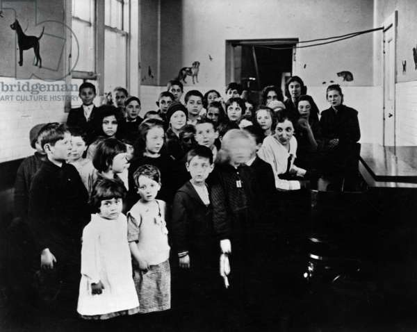 ELLIS ISLAND, c.1915 A group of immigrant children learning American songs in a classroom at Ellis Island. Photograph, c.1915.