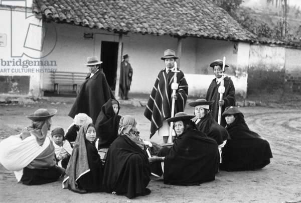 ECUADOR: MARKETPLACE Native mourners rest on the way to a funeral procession at the market town of Otavalo, Ecuador. Photographed 1955.