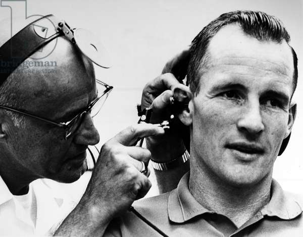 EDWARD WHITE (1930-1967) Astronaut Edward White, pilot of the Gemini IV flight, receiving a pre-flight physical examination by U.S. Navy Medical Corps Doctor Louis Ballenberger, 1 June 1965.