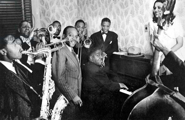COUNT BASIE (1904-1984) American musician and orchestra leader. Basie (center) with Don Byas (on saxophone, left), Henry 'Red' Allen (on trumpet, behind Basie), Pete Johnson (seated at piano), Lena Horne (atop piano), and others. Photograph, Harlem, New York, 1938.