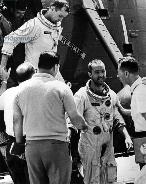 GEMINI IV: ASTRONAUTS, 1965 Gemini IV astronauts James McDivitt (on deck) and Edward White (stepping from helicopter) are welcomed aboard the USS Wasp as they emerge from their rescue helicopter that retreived them from the ocean after completing their mission, 7 June 1965.