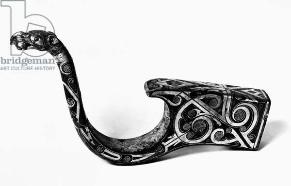 CHINA: CHARIOT FITTING Bronze chariot fitting with silver inlay, featuring a handle in the form of a long-necked dragon holding a bead in its mouth. Late Eastern Zhou, 3rd century B.C.