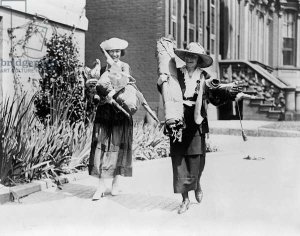 SUFFRAGETTES, c.1920 Suffragettes Julia Emory and Bertha Graf carrying bundles of flags and banners after a demonstration, c.1920.