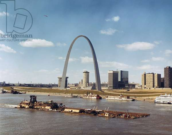 ST. LOUIS: WATERFRONT A dredge of the U.S. Army Corps of Engineers passing the Gateway Arch on the Mississippi River waterfront in St. Louis, Missouri. Photographed c.1973.