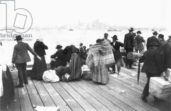 ELLIS ISLAND, c.1900 Immigrants on a dock overlooking New York Harbor. Photograph, c.1900.