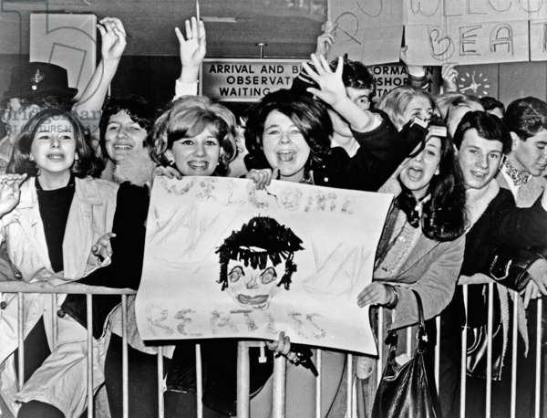 THE BEATLES, 1964 Screaming fans greeting the Beatles upon their arrival at John F. Kennedy Airport in New York City. Photograph, February 1964.