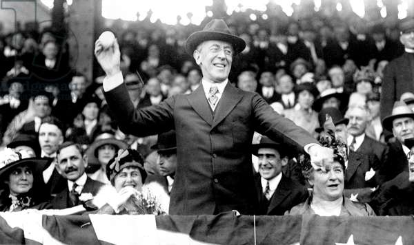 WOODROW WILSON (1856-1924) 28th President of the United States. President Wilson throwing out the ceremonial first ball on opening day of the 1916 major league baseball season, Washington, D.C. First Lady Edith Wilson smiles at left.