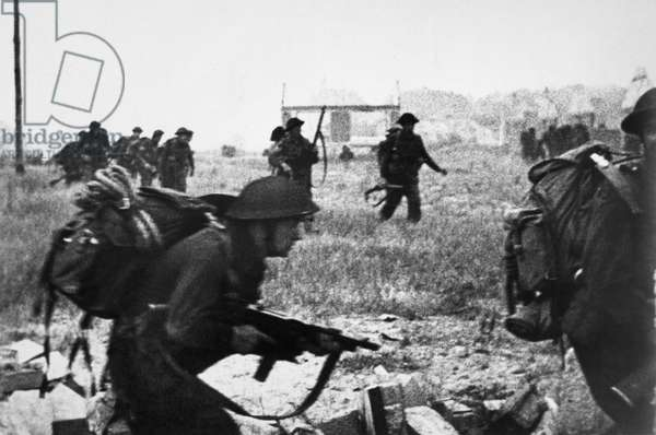 WORLD WAR II: D-DAY, 1944 British commando soldiers advance to a village during the D-Day invasion of Normandy, 6 June 1944.