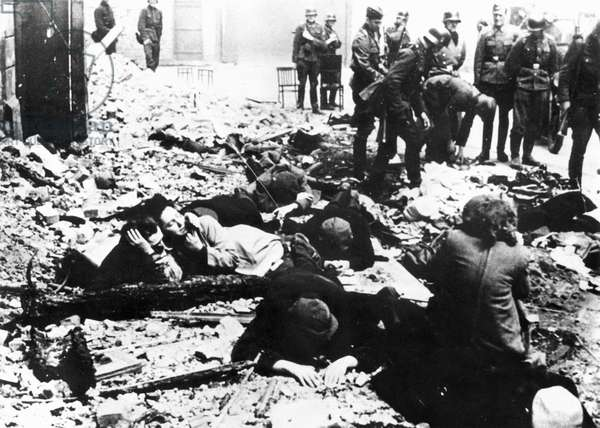WARSAW UPRISING, 1943 Jewish resistance fighters lie on the rubble after being pulled from a bunker by SS troops during the Warsaw Ghetto Uprising. Photograph, April or May 1943.
