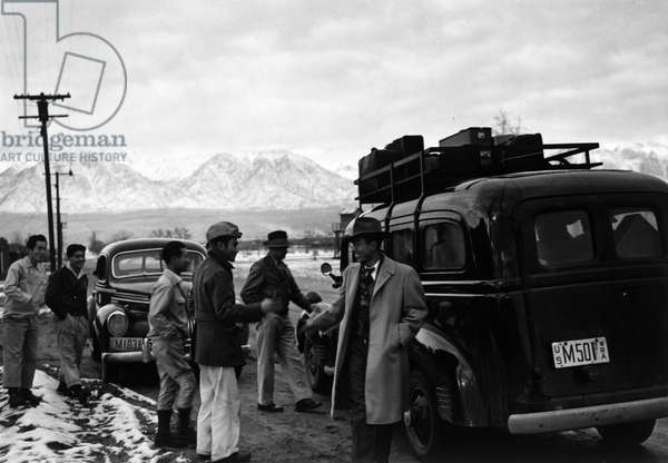 JAPANESE INTERNMENT, 1943 Group of men gathered around a car packed with passengers and luggage, about to depart from the Manzanar Relocation Center for Japanese-Americans at Owens Valley, California. Photograph by Ansel Adams, 1943.