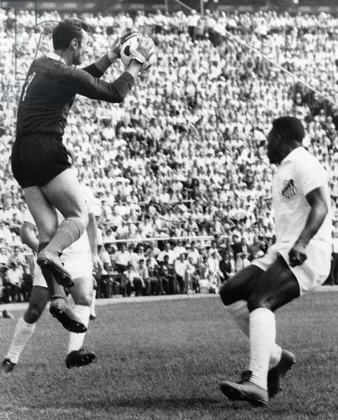 SOCCER MATCH, 1966 Pele (right) of Brazil's Santos soccer team moves in on a play as goalkeeper Costa Periera of Portugal Benfica blocks a shot, during a U.S. Cup soccer match at Randall's Island in New York City, August 1966.