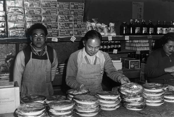JAPANESE INTERNMENT, 1943 Two men and a woman stand behind a store counter at the Manzanar Relocation Center for Japanese-Americans at Owens Valley, California. Photograph by Ansel Adams, 1943.