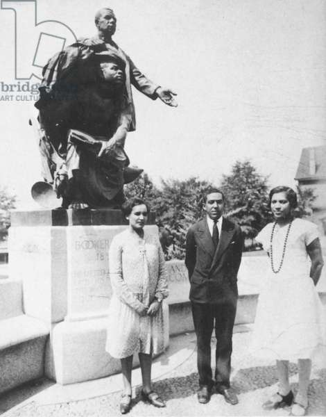HURSTON & HUGHES Zora Neale Hurston (1903-1960), American writer and anthropologist, at far right, with Jessie Fauset and Langston Hughes at Tuskegee, Alabama, posing beside a statue of Booker T. Washington in 1927.