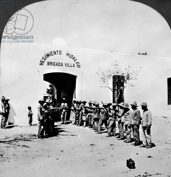 MEXICAN REVOLUTION, 1914 Armed revolutionary troops lined up outside the entrance of General Francisco 'Pancho' Villa's headquarters in Ciudad Juarez, Mexico, during the Mexican Revolution, 1914. Stereograph.