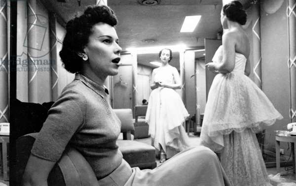 FASHION: WOMEN, 1949 Woman sitting in a chair while another woman models a gown. Photographed by Stanley Kubrick, 1949.