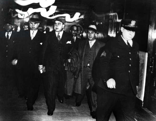 ALPHONSE CAPONE (1899-1947) American gangster. Capone (center) being escorted by federal marshals at the Chicago courthouse after being convicted for tax evasion and sentenced to prison, 1931.
