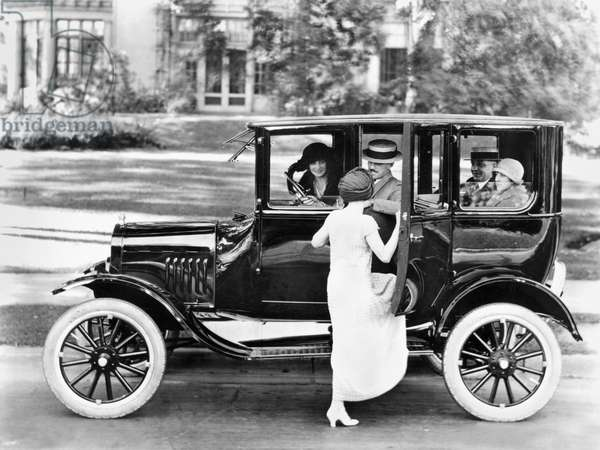 FORD SEDAN, c.1923 A woman getting into a Ford Sedan with four other passengers. Photograph, c.1923.