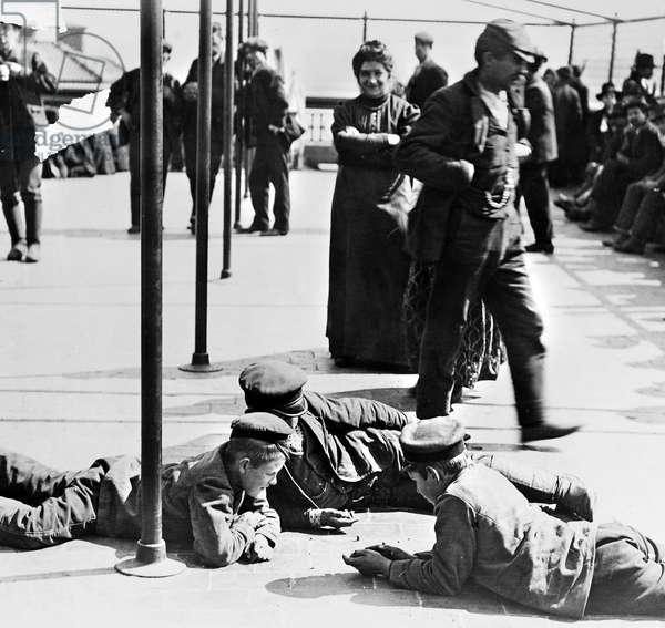 ELLIS ISLAND: IMMIGRANTS Detained immigrants awaiting approval to enter the United States, amusing themselves on the rooftop of the main building at Ellis Island, New York City. Photograph, c.1907.