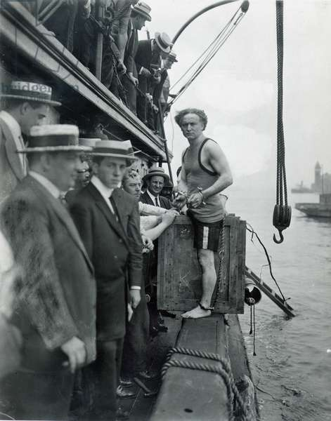 HARRY HOUDINI (1874-1926) American magician. A shackled Houdini about to be padlocked into a packing case and lowered into New York harbor, 1914.