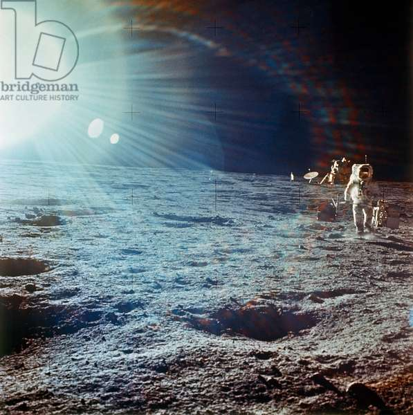 APOLLO 12, 1969 Astronaut Alan Bean carrying components of the ALSEP (Apollo Lunar Surface Experiments Package) while walking on the surface of the moon during the Apollo 12 mission, 19 November 1969, with lunar module and sun glare in the background.