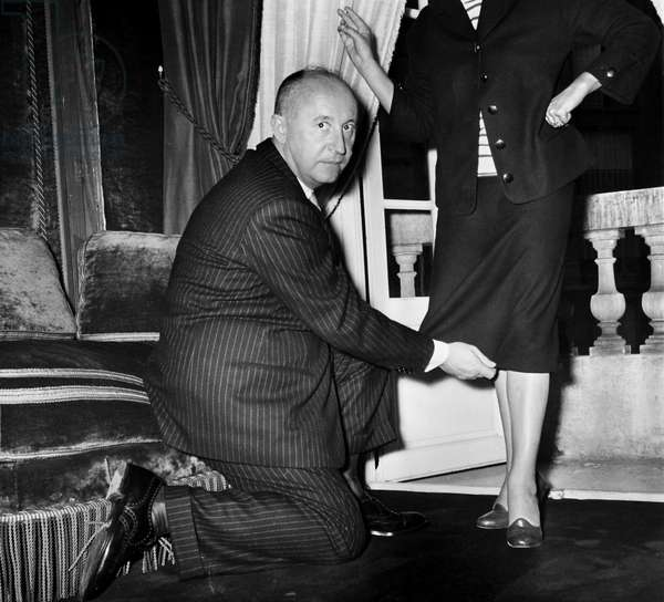 CHRISTIAN DIOR (1905-1957) French fashion designer. Dior demonstrating his new skirt length, July 1953.
