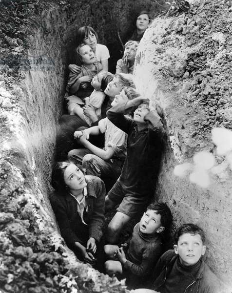 WWII: BATTLE OF BRITAIN Children taking shelter in a trench during the Battle of Britain. Photograph by John Topham, 1940.