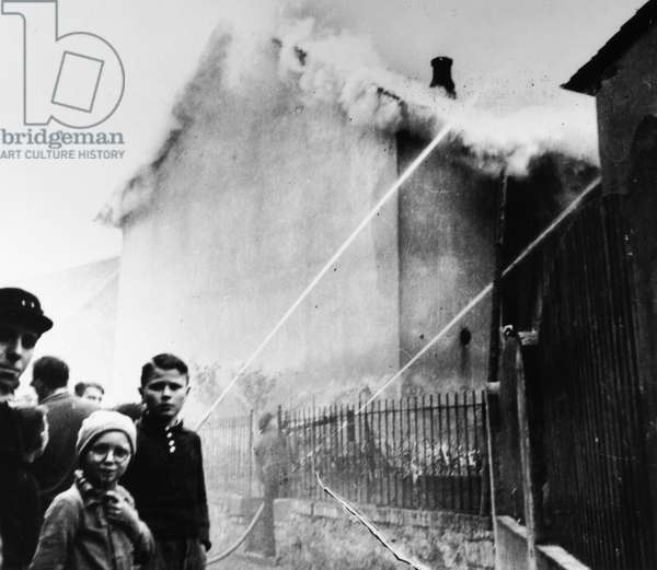 KRISTALLNACHT, 1938 Residents of Ober-Ramstadt, Germany, watch as local firefighters work to prevent fires from spreading from the synagogue to nearby homes, while permitting the synagogue to continue burning in the aftermath of the Kristallnacht pogrom, 9-10 November 1938.