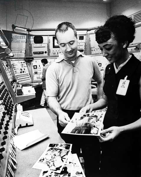 JAMES McDIVITT (1929-) Astronaut James McDivitt, command pilot of the Gemini IV mission, reviews photographs of recent flight preparation activities with NASA Still Photo Desk coordinator, Margaret Ware, May 1965.