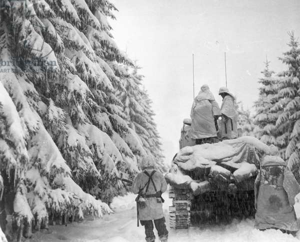 WWII: BATTLE OF THE BULGE Tanks and infantrymen of the 82nd Airborne Division push through the snow in Belgium: December 1944.